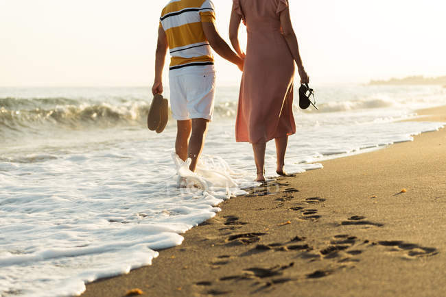 Back view of barefoot man and woman holding hands and carrying shoes while walking on sandy beach — Stockfoto