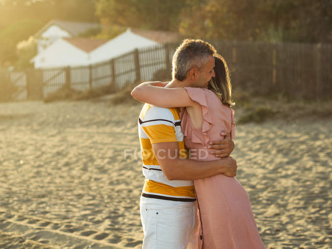 Excited adult man and woman laughing and embracing each other while having fun on sandy shore on resort — Stock Photo