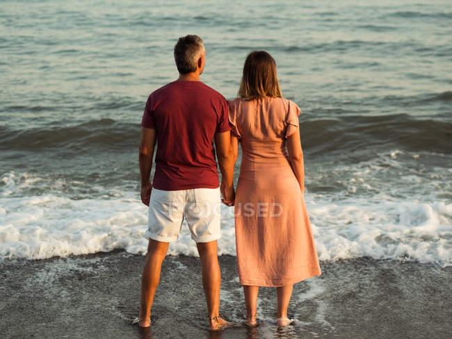 Rückansicht des Paares, das sich an den Händen hält und auf das winkende Meer blickt — Stockfoto
