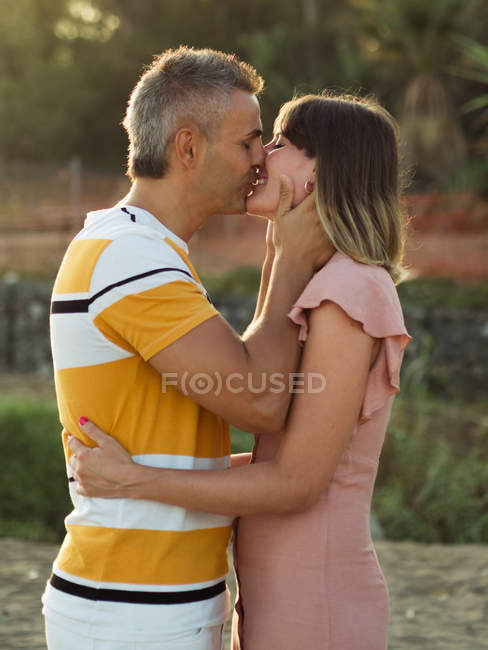 Mid adult couple embracing and kissing outdoors — Stock Photo