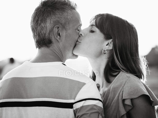 Woman kissing happy man outdoors — Stock Photo