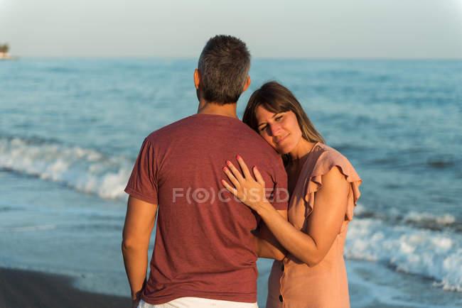 Erwachsene Frau stützt sich auf Mann, während sie am Strand in der Nähe des winkenden Meeres steht — Stockfoto