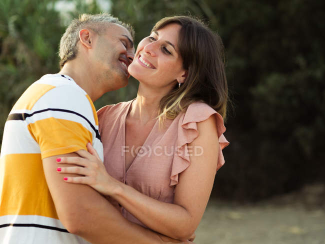 Man embracing and kissing mid adult woman with happy smile — Stock Photo