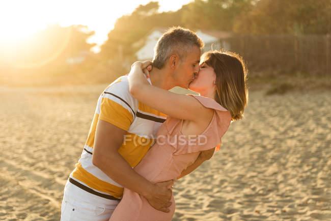 Взрослые мужчины и женщины целуются и обнимаются на песчаном берегу курорта — стоковое фото