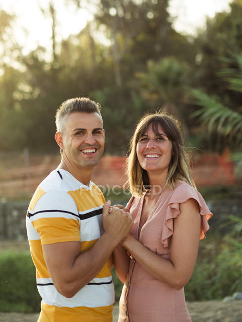 Side view of adult man and woman holding hands and looking in camera with happy smile — Stock Photo