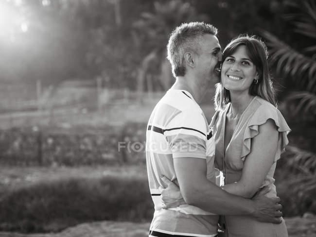 Мужчина обнимает и целует среднюю взрослую женщину с счастливой улыбкой — стоковое фото