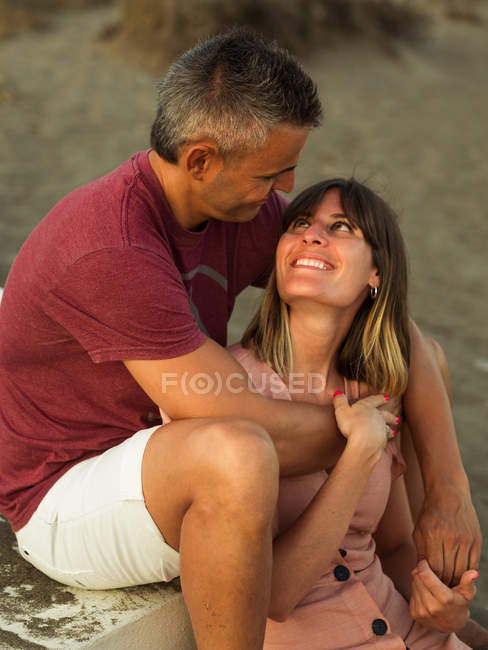 Cheerful adult man and woman smiling and embracing while sitting on steps outside building — Stock Photo