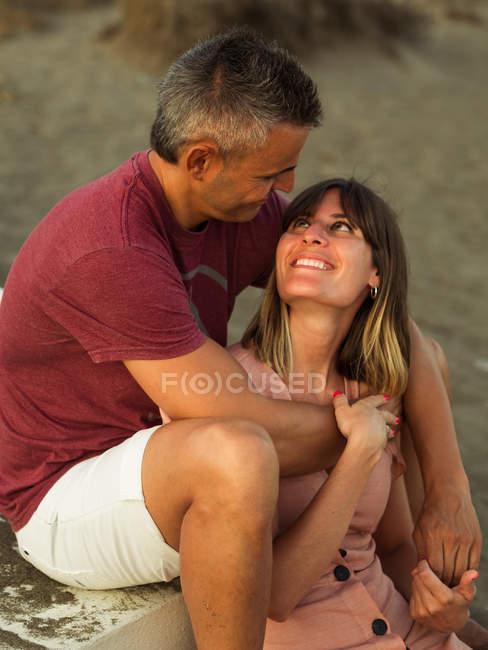 Веселий дорослий чоловік і жінка посміхаються і обіймаються, сидячи на сходах біля будинку. — стокове фото