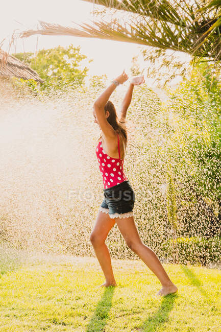 Excited teen girl laughing and playing with jet of clean water while having fun in garden on sunny day — Stock Photo