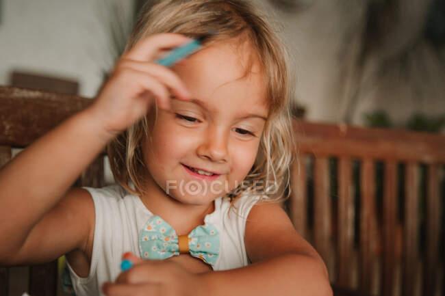 Сосредоточенная маленькая девочка, опирающаяся на стол и раскрашивающие картинки у книги маркером на размытом фоне комнаты дома — стоковое фото