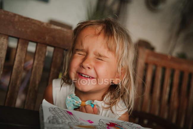 Очаровательная маленькая девочка, щурящаяся и улыбающаяся, сидя за столом с раскраской и ожидая сюрприз дома — стоковое фото