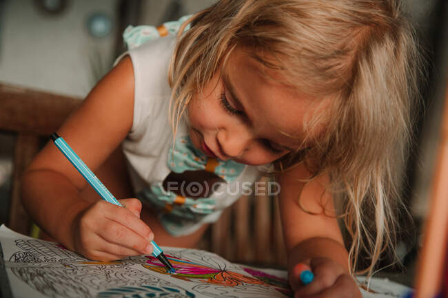 Focused little girl leaning on table and coloring pictures at book with marker pen on blurred background of room at home — Stock Photo