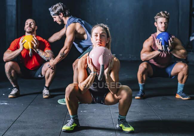 Мускулистые ребята с тренером поднимают колокольчики чайника во время функциональной тренировки в современном оздоровительном клубе — стоковое фото