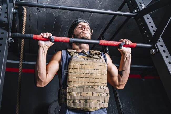 Сильный мужчина делает подтянутые вправи с весом на горизонтальном баре — стокове фото