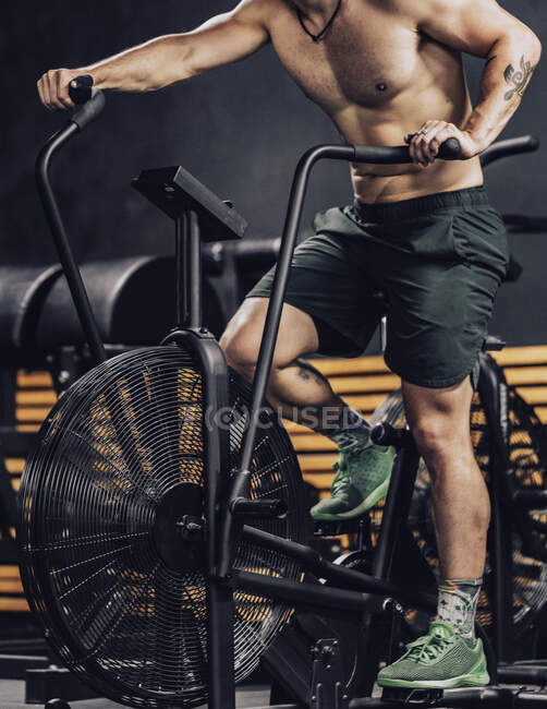 Strong man training on contemporary exercise bike in sport club — Stock Photo