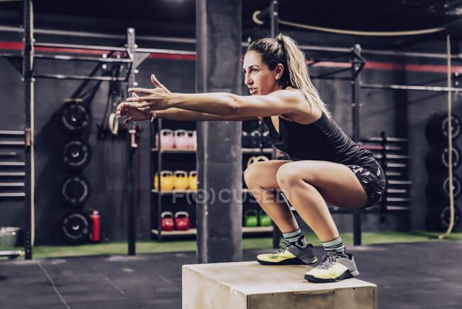 Спортивная женщина прыгает на коробке, чтобы улучшить выносливость в тренажерном зале — стоковое фото