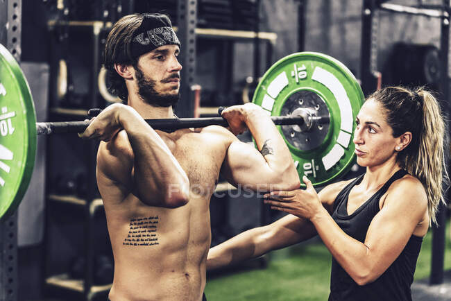 Strong coach in sportswear helping athletic client and doing barbell workout in modern gym — Stock Photo