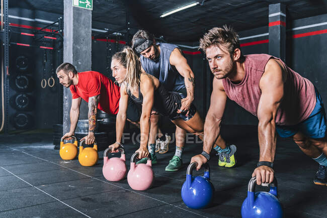 Athletic strong fellows doing workout with weight in gym - foto de stock