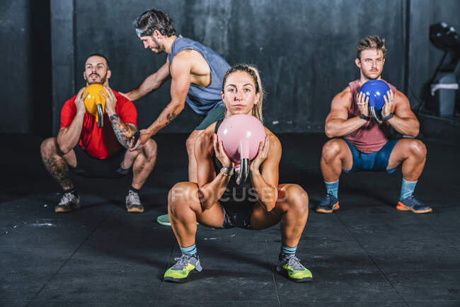 Athletic strong fellows doing workout with weight in gym — Stock Photo