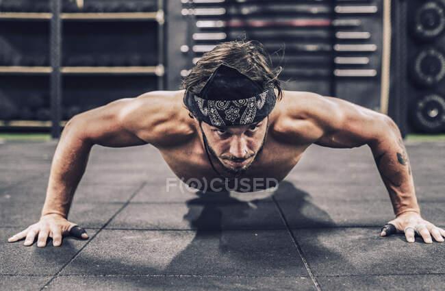 Сильный и спортивный мужчина делает отжимания тренировки в современном тренажерном зале — стоковое фото