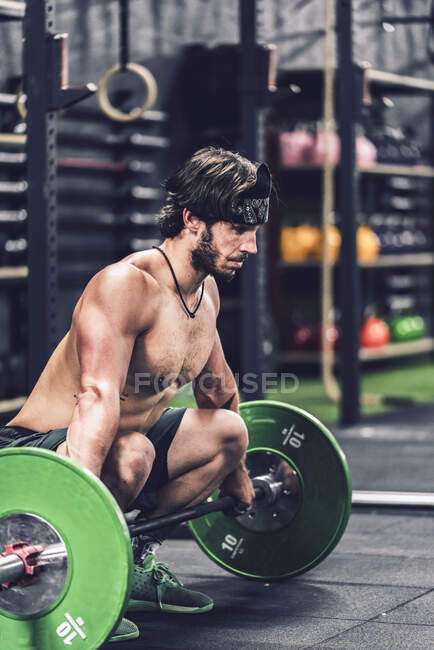 Strong and athletic man doing barbell workout in modern gym — Stock Photo