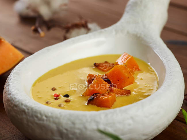 Orange and ginger soup with pumpkin pieces in fancy porcelain bowl — Stock Photo