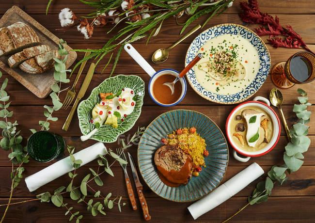 Зверху зелені рослини розміщують навколо різних смачних страв на дерев'яній стільниці — стокове фото