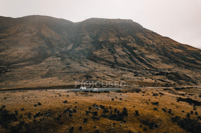 Peaceful cliff of rocky mountain range with slope near highway parking caravans — Stock Photo