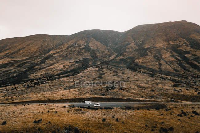 Мирный утес скалистой горной цепи с склоном возле автофургонов — стоковое фото