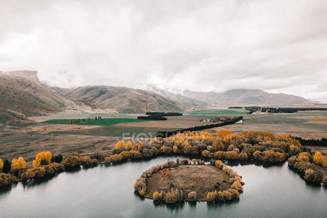 Lago de montaña tranquilo rodeado de colinas y árboles brillantes con follaje anaranjado en un día misterioso. - foto de stock