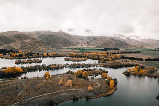 Peaceful mountain lake surrounded with hills and bright trees with orange foliage on misty day — Stock Photo