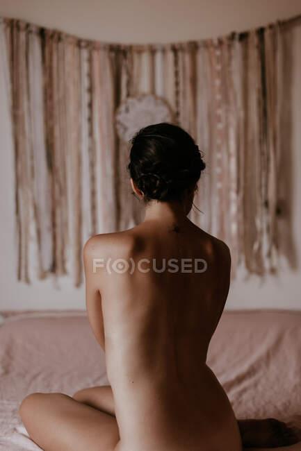Голая женщина сидит на кровати — стоковое фото