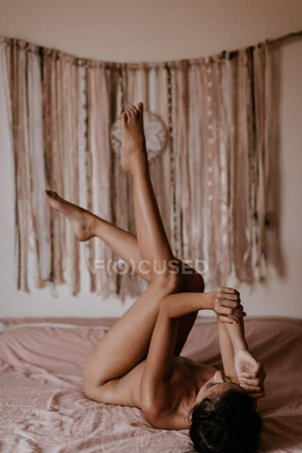 Naked woman lying on bed — Stock Photo