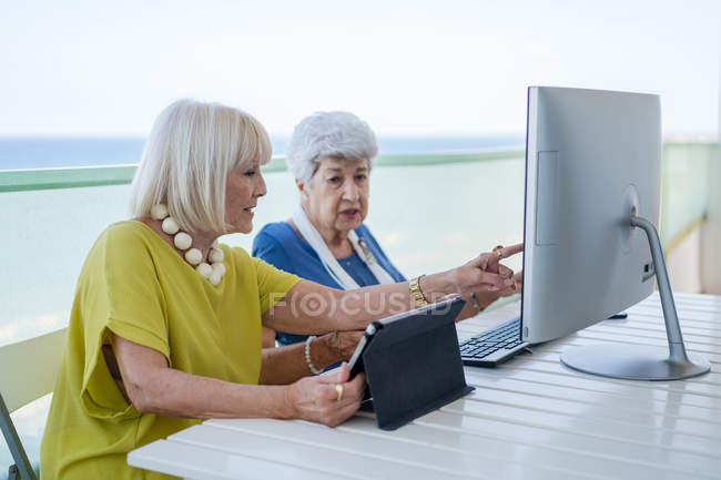 Stylish old friends browsing social media on tablet while sitting at table with computer on balcony on resort — Stock Photo