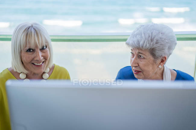 Stylish old friends sitting at table with computer on balcony on resort — Stock Photo