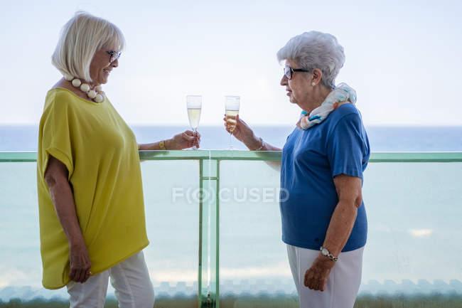 Glückliche Frauen in eleganten Outfits prosten sich zu und genießen Wein, während sie auf dem Hotelbalkon am Meer am Urlaubsort stehen — Stockfoto