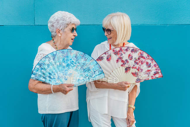 Positive trendy aged grey-haired females waving with big color hand fans, looking at each other on blue background — Stock Photo