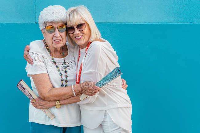 Positive trendige grauhaarige Frauen mit großen farbigen Handfächern, die sich umarmen — Stockfoto