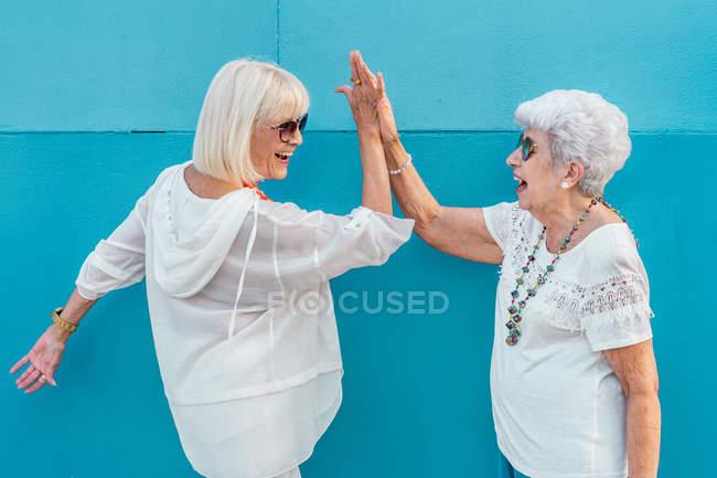 Seitenansicht von lachenden, fröhlichen älteren grauhaarigen Frauen mit Sonnenbrille, die High Five geben — Stockfoto