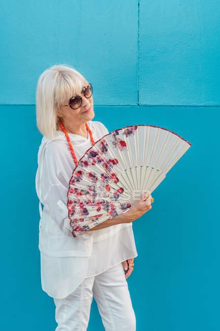 Элегантная пожилая женщина с веером улыбается и смотрит в камеру, стоя напротив голубой стены в жаркий день на курорте — стоковое фото