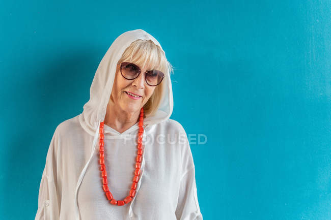 Portrait of beautiful stylish white-haired senior woman with sunglasses in white shirt with hood on head and coral beads — Stock Photo