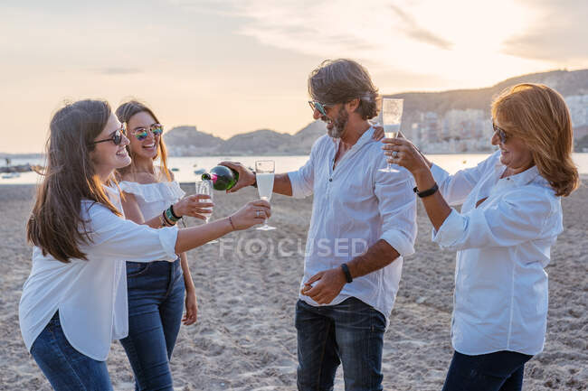 Cheerful mature parents and young daughters clinking glasses of wine and laughing while celebrating family reunion in evening on resort — Stock Photo