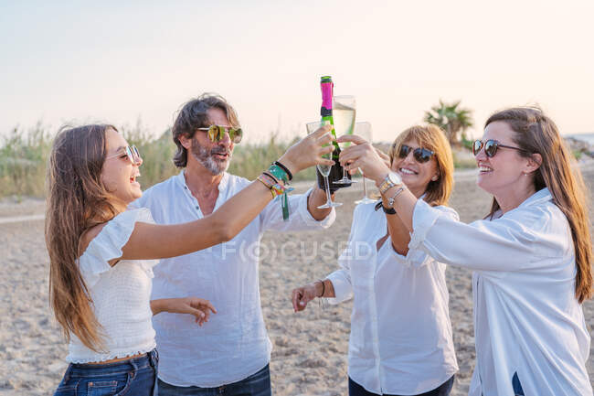 Fröhlich erwachsene Eltern und kleine Töchter klimpern mit Weingläsern und lachen, während sie abends im Resort ein Familientreffen feiern — Stockfoto
