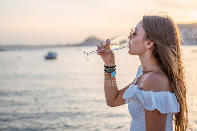Side view of happy young female with closed eyes drinking wine while standing near sea in evening on resort — Stock Photo
