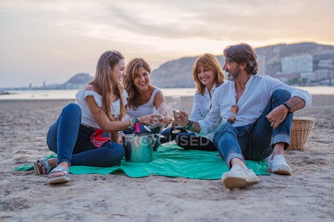Happy family drinking wine during picnic on beach — Stock Photo