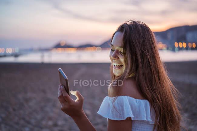 Назад вид счастливой молодой женщины, улыбающейся и просматривающей социальные сети на смартфоне, проводя время на песчаном пляже вечером — стоковое фото