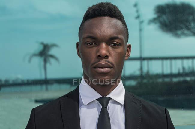 Афроамериканский молодой задумчивый бизнесмен в костюме смотрит в камеру на стеклянном фоне с отражением — стоковое фото
