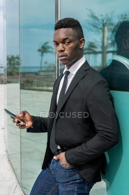 Seitenansicht des schwarzen trendigen Unternehmers, der mit dem Handy surft und die Hand in der Tasche hält, während er sich an die Glasscheibe auf der Straße lehnt — Stockfoto