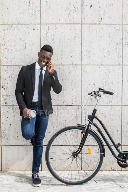 Enthousiaste optimiste homme d'affaires afro-américain parlant au téléphone et tenant un café pendant la pause du vélo — Photo de stock