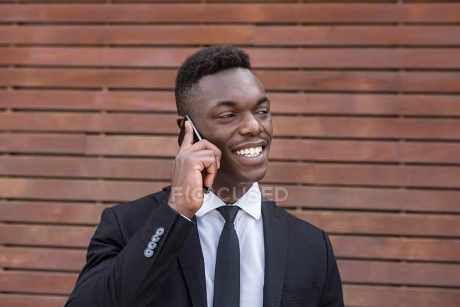 Positivo sorridente uomo d'affari afroamericano di successo che parla sul cellulare accanto alla parete di legno a strisce urbane — Foto stock